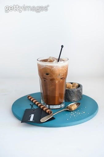 A glass of hazelnut iced coffee, brown sugar cubes and a wafer roll - gettyimageskorea
