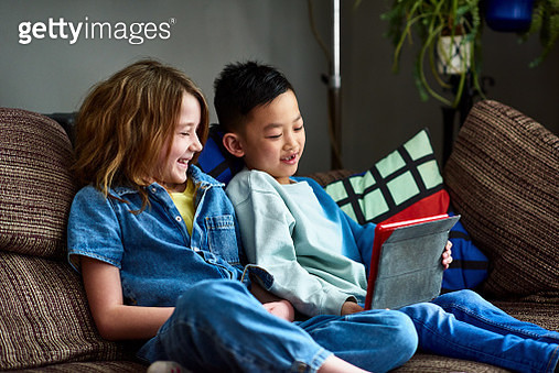 Boy and girl sitting on sofa playing online, learning, education, multiracial group - gettyimageskorea