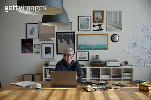 Happy female senior artist working at laptop in studio - gettyimageskorea