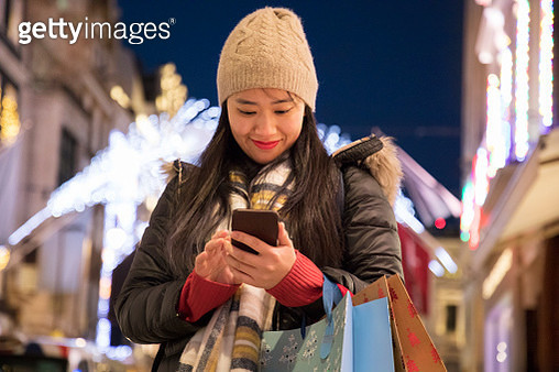 Asain woman checks mobile phone during christmas shopping. - gettyimageskorea