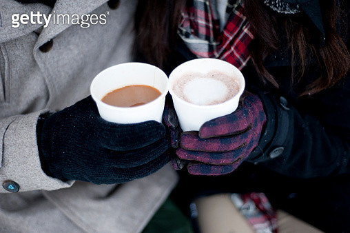Young couple in winter gloves holding takeaway drinks, close up of hands - gettyimageskorea