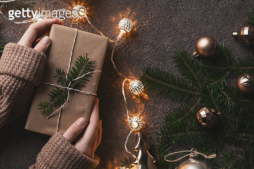 Male hand holding vintage gift box with tree. Christmas card - gettyimageskorea