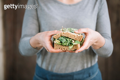 Midsection of woman holding sandwich while standing at home - gettyimageskorea