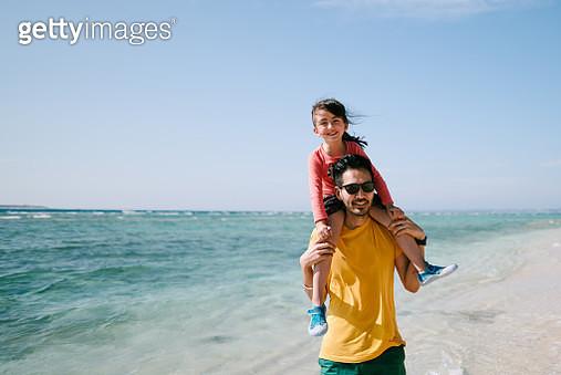 Father carrying preschool girl on shoulders on tropical beach, Okinawa, Japan - gettyimageskorea