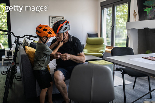 Grandfather and grandson sitting in living room and fitting cycling helmets - gettyimageskorea