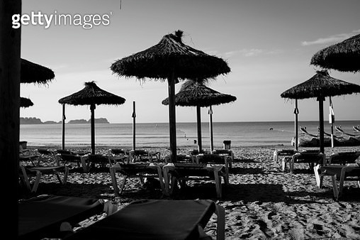 Lounge Chairs And Parasols At Beach Against Sky - gettyimageskorea