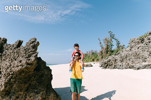 Father giving little girl piggyback ride on tropical beach, Okinawa, Japan - gettyimageskorea