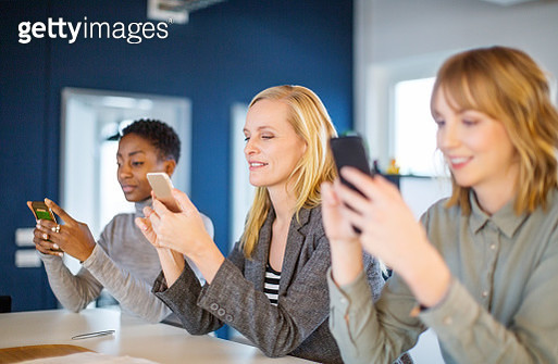Group of three businesswomen sitting at meeting table and using mobile phones. Multi-ethnic business colleagues using mobile phone's in the office. - gettyimageskorea