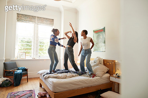 Full length of cheerful young female friends enjoying while dancing on bed at home during slumber party - gettyimageskorea