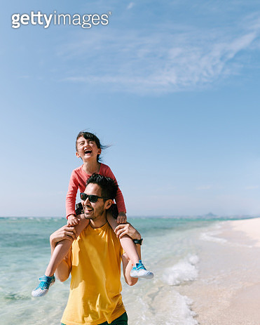 Father carrying his preschool daughter on shoulders and walking on white sand tropical beach, Okinawa, Japan - gettyimageskorea