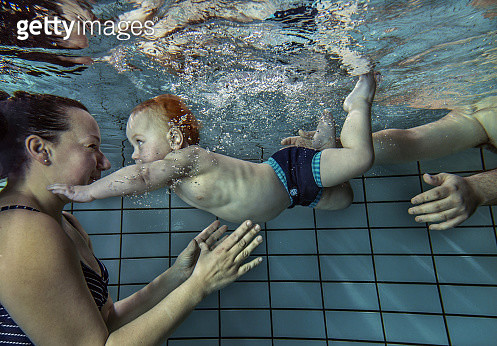 Mother and child swimming together underwater. - gettyimageskorea