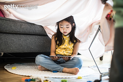 Young girl using tablet in homemade fort at home - gettyimageskorea