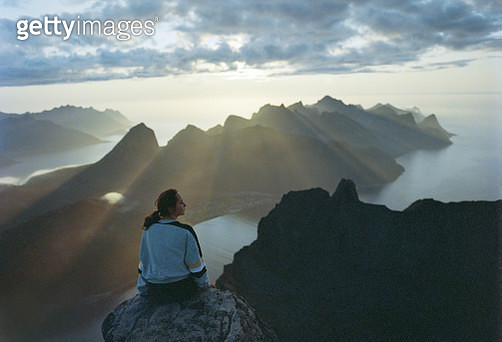 Young Caucasian sitting on rock and looking at wonderful view Senja Island from mountains - gettyimageskorea