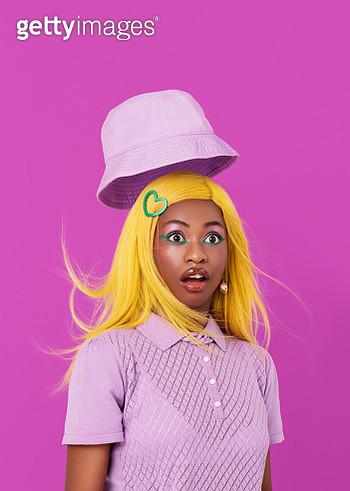 Studio portrait of girl with yellow hair so surprised that her hat flies off her head. - gettyimageskorea