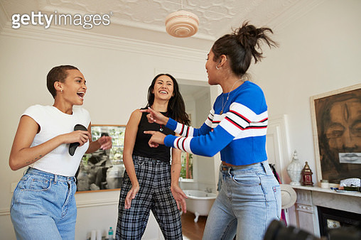 Happy young women singing and dancing in bedroom at home during slumber party - gettyimageskorea