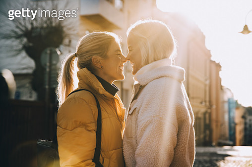 Happy woman embracing female partner with closed eyes while standing in city - gettyimageskorea