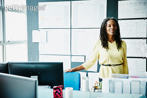 Smiling businesswoman standing in office - gettyimageskorea