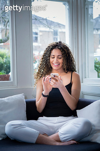Smiling woman sitting near window texting on cell phone - gettyimageskorea