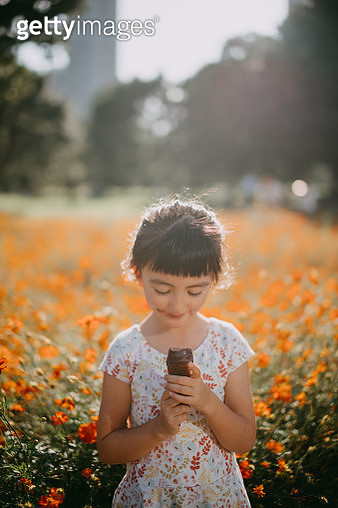 Adorable 5 year old mixed race girl enjoying chocolate ice cream in flower field - gettyimageskorea