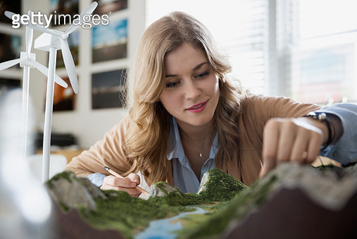 Engineer assessing wind turbine and landscape models - gettyimageskorea