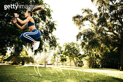 Young woman training, jumping between agility hurdles in park - gettyimageskorea