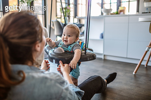 Playful mother with her baby boy at home.Cute little baby boy enjoying on a swing while his mother swings him at home. - gettyimageskorea