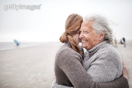 Affectionate grandmother and granddaughter hugging on the beach - gettyimageskorea