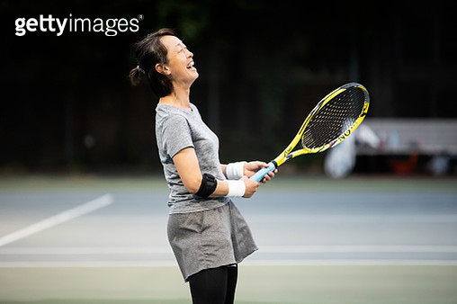 A woman who enjoys tennis at night - gettyimageskorea
