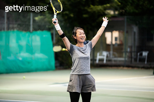A woman who expresses joy in winning a tennis game - gettyimageskorea