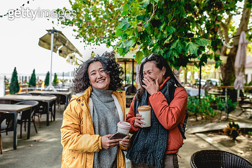 Portrait of two Asian women outside together talking and laughing. They are holding reusable coffee cup - gettyimageskorea