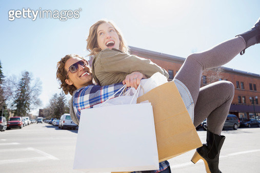 Playful couple on sunny urban street - gettyimageskorea
