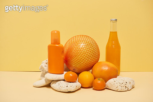 Citrus fruits, orange soda and sun cream bottle arranged on natural chalk stone on yellow background. - gettyimageskorea