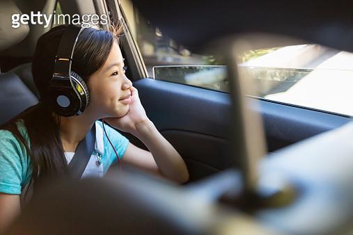 Girl listening to headphones in back seat of car - gettyimageskorea