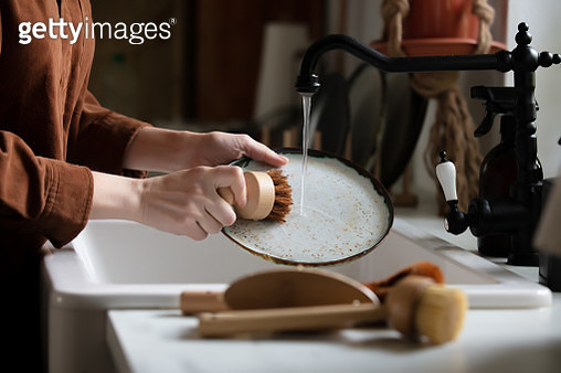 woman washes a plate in the kitchen using eco-friendly brushes - gettyimageskorea