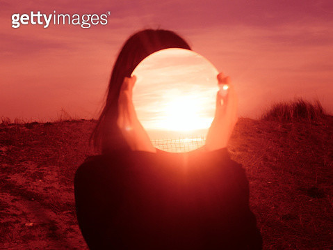 Woman Holding Mirror Against Face While Standing Outdoors During Sunset - gettyimageskorea