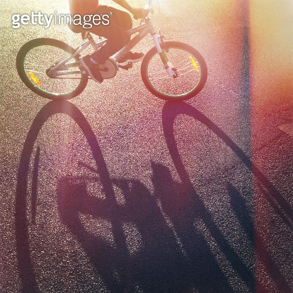 Long afternoon shadow of child riding bicycle - gettyimageskorea