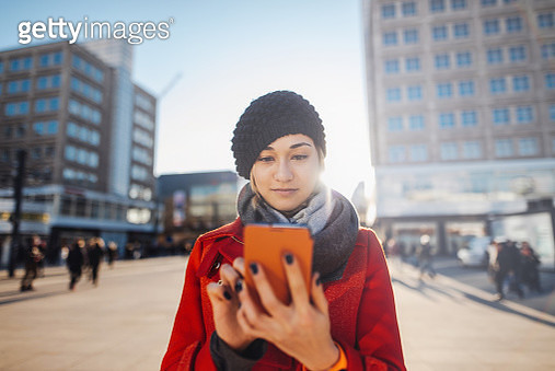 Young woman using smartphone in city. - gettyimageskorea