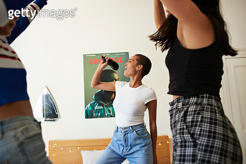 Young woman singing while holding hairbrush and dancing with friends in bedroom - gettyimageskorea