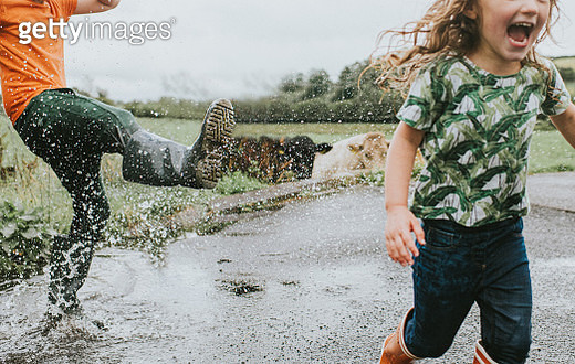 Two children in welly boots play in a Huge Puddle - gettyimageskorea