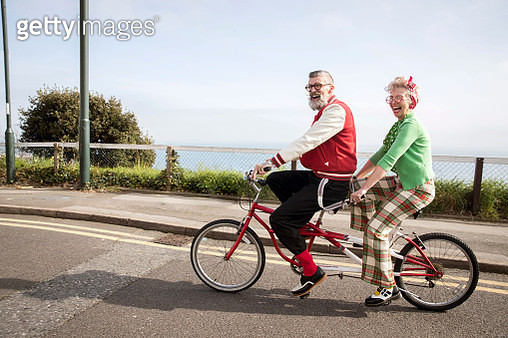Quirky couple sightseeing on tandem bicycle, Bournemouth, England - gettyimageskorea