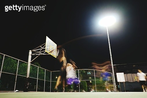 Blurred Motion Of People Playing Basketball In Court At Night - gettyimageskorea
