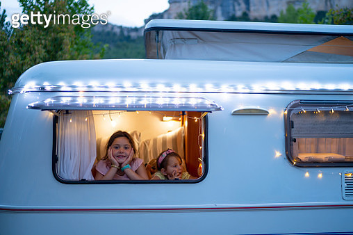 Sisters looking through window of illuminated motor home at dusk - gettyimageskorea
