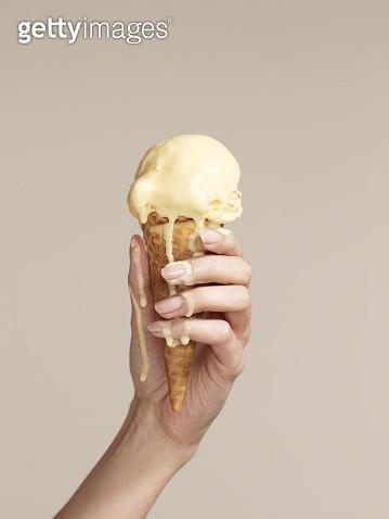 Woman holding melting ice cream cone - gettyimageskorea