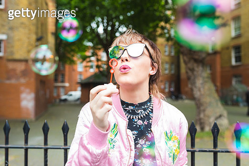 Retro styled young woman blowing bubbles - gettyimageskorea