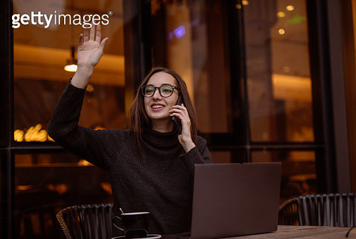 One woman, beautiful lady sitting in cafe on coffee break talking on mobile phone and using laptop. - gettyimageskorea