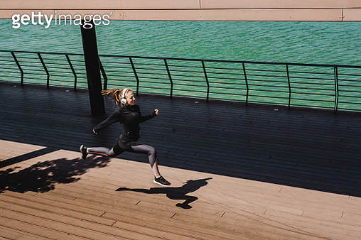 Young sporty woman running and jumping in the modern district by the sea - gettyimageskorea