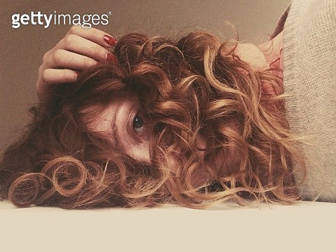 A portrait of a young woman with long curly hair lying down and looking at camera - gettyimageskorea
