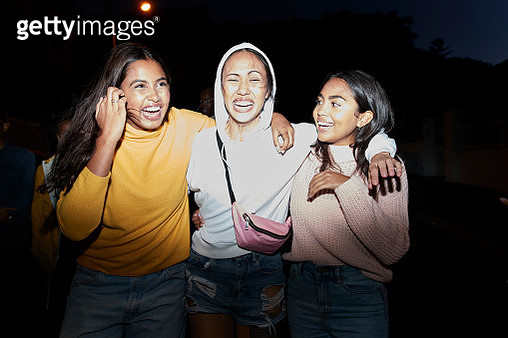 Cheerful female friends with arm around walking together at night - gettyimageskorea