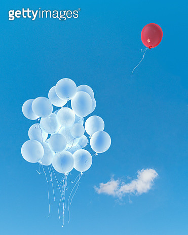 Red balloon flying away from white balloons against blue sky - gettyimageskorea