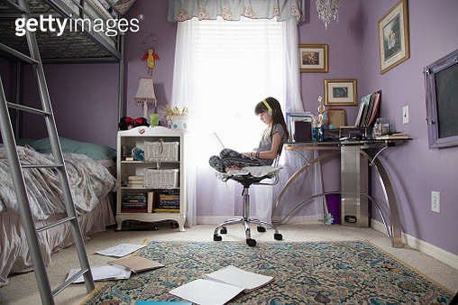 Girl in her bedroom using laptop with headphones - gettyimageskorea